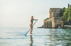 Young beautiful slavian woman tourist practicing paddle boarding, Alanya royalty free stock photos
