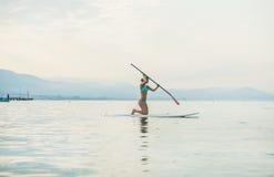 Young beautiful slavian woman tourist practicing paddle boarding Stock Photo