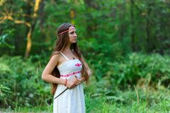 A young beautiful Slavic girl with long hair and Slavic ethnic dress stands in a summer forest with a ritual dagger in her hands Stock Photos