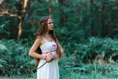 A young beautiful Slavic girl with long hair and Slavic ethnic dress stands in a summer forest with a ritual dagger in her hands Stock Photography