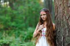 A young beautiful Slavic girl with long hair and Slavic ethnic dress stands in a summer forest with a ritual dagger in her hands Stock Photo
