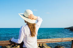 Young beautiful slender woman with long hair holding sunhat from wind in boho style clothes at the shore looking and the sea Stock Images