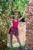 Young beautiful slim blond girl with long hair in a red dress walks among the ruins of the destruction of an urbex industrial buil Stock Photography