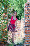 Young beautiful slim blond girl with long hair in a red dress walks among the ruins of the destruction of an urbex industrial buil Royalty Free Stock Images