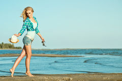 Young beautiful slim blond girl is running along the seaside with hat and sunglasses in her hands. Stock Images
