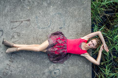 Young beautiful slim girl with long hair blindinka lies in a red dress on a concrete slab, his head hanging over the water in the Stock Photo