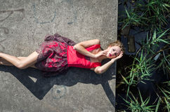 Young beautiful slim girl with long hair blindinka lies in a red dress on a concrete slab, his head hanging over the water in the Stock Photos