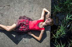 Young beautiful slim girl with long hair blindinka lies in a red dress on a concrete slab, his head hanging over the water in the Royalty Free Stock Image