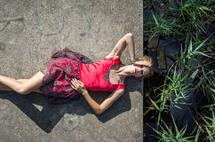 Young beautiful slim girl with long hair blindinka lies in a red dress on a concrete slab, his head hanging over the water in the Stock Image