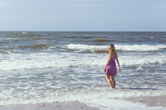 Young beautiful slim girl standing on the beach on a sunny summer day, a strong wind on the sea Royalty Free Stock Photography