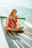Young beautiful slim sexy girl in bikini and pareo is resting on cruise on a private sailing yacht. Young beautiful slim sexy girl in bikini and pareo is resting royalty free stock images