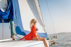 Young beautiful slim sexy girl in bikini and pareo is resting on cruise on a private sailing yacht. Young beautiful slim sexy girl in bikini and pareo is resting stock photos