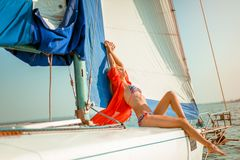 Young beautiful slim sexy girl in bikini and pareo is resting on cruise on a private sailing yacht. Young beautiful slim sexy girl in bikini and pareo is resting stock images