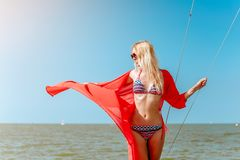 Young beautiful slim sexy girl in bikini and pareo is resting on cruise on a private sailing yacht. Young beautiful slim sexy girl in bikini and pareo is resting royalty free stock photography