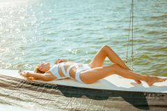 Young beautiful slim sexy girl in bikini and pareo is resting on cruise on a private sailing yacht. Young beautiful slim sexy girl in bikini is resting on a stock photography