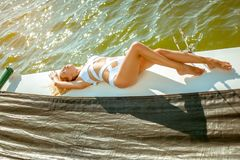 Young beautiful slim sexy girl in bikini and pareo is resting on cruise on a private sailing yacht. Young beautiful slim sexy girl in bikini is resting on a stock image
