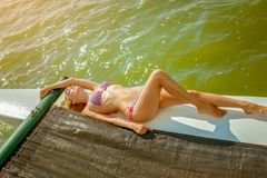Young beautiful slim sexy girl in bikini and pareo is resting on cruise on a private sailing yacht. Young beautiful slim sexy girl in bikini is resting on a stock photos