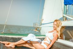 Young beautiful slim sexy girl in bikini and pareo is resting on cruise on a private sailing yacht. Young beautiful slim sexy girl in bikini is resting on a royalty free stock photos