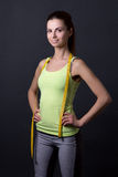 Young beautiful slim sporty woman with measure tape over grey Royalty Free Stock Images