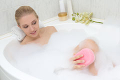 Young beautiful slim woman bathing with sponge Royalty Free Stock Image