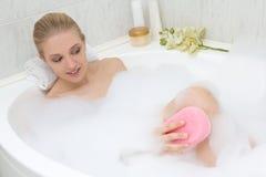 Young beautiful slim woman bathing with sponge Royalty Free Stock Image