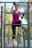 Young beautiful slim woman in bright sportswear climbs up on the ladder at outdoor sportsground. White earphones, protective glove royalty free stock photo
