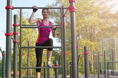 Young beautiful slim woman in bright sportswear climbs up on the ladder at outdoor sportsground. White earphones, protective glove stock photography