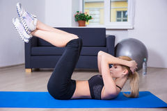 Young beautiful slim woman doing exercises for abdominal muscles Stock Photos