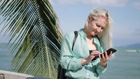 Beautiful slim woman with long blonde hair and green shirt standing near palm tree and using smartphone over background. Young beautiful slim woman with long stock video