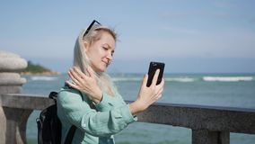 Beautiful slim woman with long blonde hair in sunglasses and green shirt standing near palm tree and making selfie on. Young beautiful slim woman with long stock video footage
