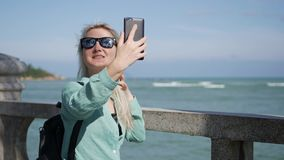 Beautiful slim woman with long blonde hair in sunglasses and green shirt standing near palm tree and making selfie on. Young beautiful slim woman with long stock video