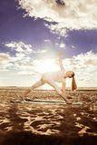 Young beautiful slim woman practices yoga on the beach at sunris Royalty Free Stock Photography