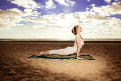 Young beautiful slim woman practices yoga on the beach at sunris Stock Photos