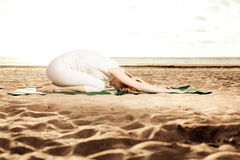 Young beautiful slim woman practices yoga on the beach at sunris Royalty Free Stock Image