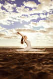 Young beautiful slim woman practices yoga on the beach at sunris Stock Photo
