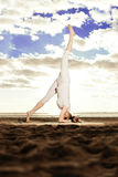 Young beautiful slim woman practices yoga on the beach at sunris Stock Image