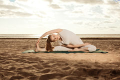 Young beautiful slim woman practices yoga on the beach at sunris Royalty Free Stock Images