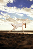 Young beautiful slim woman practices yoga on the beach at sunris Stock Photography