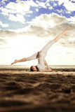 Young beautiful slim woman practices yoga on the beach at sunris Royalty Free Stock Photo