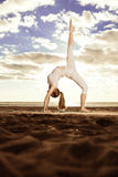 Young beautiful slim woman practices yoga on the beach at sunset Stock Image