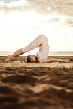 Young beautiful slim woman practices yoga on the beach at sunset Royalty Free Stock Photo