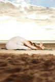 Young beautiful slim woman practices yoga on the beach at sunset Royalty Free Stock Images