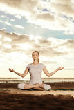 Young beautiful slim woman practices yoga on the beach at sunset Stock Photo