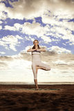 Young beautiful slim woman practices yoga on the beach at sunset Royalty Free Stock Image