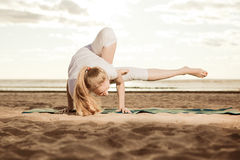 Young beautiful slim woman practices yoga on the beach at sunset Royalty Free Stock Photos