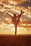Young beautiful slim woman silhouette practices yoga on the beac Stock Image