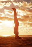 Young beautiful slim woman silhouette practices yoga on the beac Stock Photography