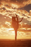 Young beautiful slim woman silhouette practices yoga on the beac Royalty Free Stock Image