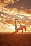 Young beautiful slim woman silhouette practices yoga on the beac Royalty Free Stock Images