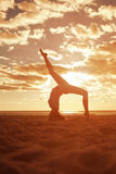 Young beautiful slim woman silhouette practices yoga on the beac Stock Images